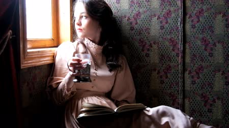 çay fincanı : Young woman dressed in retro dress sitting in old train compartment and reading book drinking tea