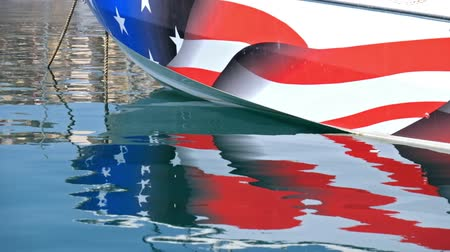 flange : Reflection of Yacht board with american flag in calm water