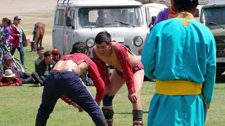 grapple : KHOVD, MONGOLIA - JULY 06, 2017:  Mongolian wrestlers wrestling in nature. Spectators in national clothes watch the competition. Stock Footage