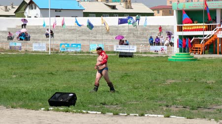 grapple : ALTAI CITY, MONGOLIA - JULY 06, 2017:  Overweight mongolian wrestler crossing sport stadium of Altai city in south-west of Mongolia.