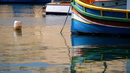 maltština : Fore of national maltese bout luzzu in malta harbor with reflection in calm water