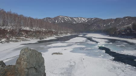frazil ice : Video panorama of Altai river Katun near Elekmonar settlements with floating on ice in water and mountains on background in winter season, Siberia, Russia