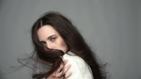 barna haj : Slow motion video portrait of beauty young brunette woman portrait with green eyes and streaming hair in white fashion female jacket on gray background