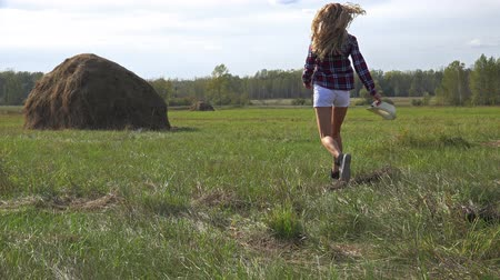 jump away : Blonde pretty happy country girl running away and jumping in the field among haystacks