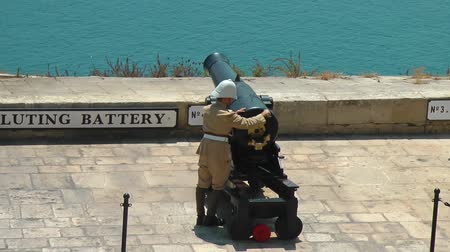 water cannon : VALLETTA, MALTA - JULY 24, 2015: Cannons of the Saluting Battery. Soldier charges gun. Upper Barrakka Gardens in Valletta, Malta