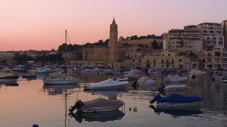 maltština : MARSASKALA, MALTA - JULY 31, 2015: The night view of Marsaskala parish church of St. Anna (St. Anne) over the Marsaskala bay with the traditional Maltese fishing boats (Luzzu). Malta