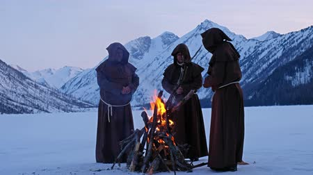 hacı : Group of monks in brown cloaks of the order of St. Francis are warming themselves by the fire on the mountains