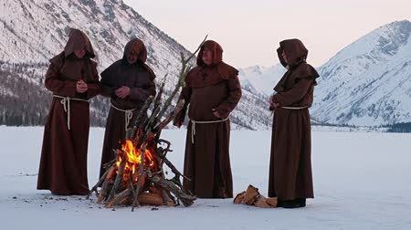 rito : Group of monks in brown cloaks of the order of St. Francis are warming themselves by the fire on the mountains