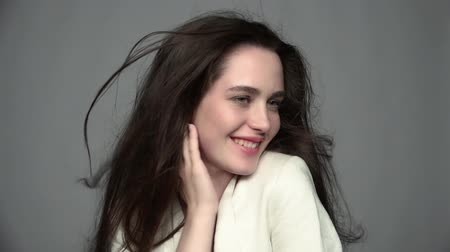 desgrenhado : Slow motion video portrait of beauty young brunette smiling woman with green eyes and streaming hair in white fashion female jacket on gray background