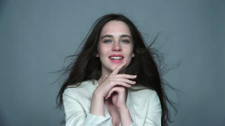 Video portrait of happy smiling young brunette woman with green eyes and streaming hair in white fashion female jacket on gray background