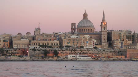 View on Valletta St. Pauls Anglican Cathedral and belltower of Charmelite Church from Sliema embankment at the Sunset time, Malta Stock mozgókép