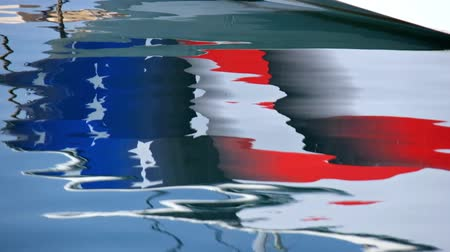 Reflection of Yacht board with american flag in calm water