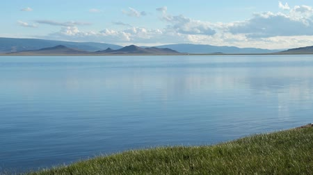 Calm waters of mongolian lake Telmen surrounded by hills and clouds Stock mozgókép