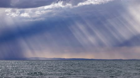 ás : Rain and sun rays through the sky over mongolian lake Durgen Nuur. Khovd province, Western Mongolia.