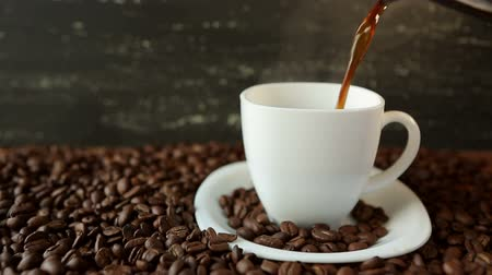 black coffee : Pouring coffee in cup surrounded by coffee beans
