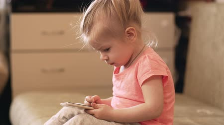 использование : Little baby girl playing with phone at home. UHD shot.
