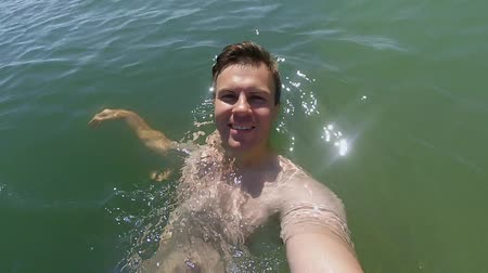 один человек : Young athletic man making selfie in the sea and swims on the back