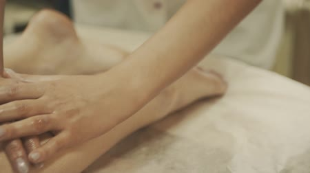 tendo : Woman having feet massage with hot stone, close up. Masseur kneads foot and leg