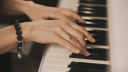 půltón : Female hands playing piano. Woman touches fingers on keys. Close up