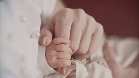 holding : Young mother holding newborns hand. Close up in slow motion