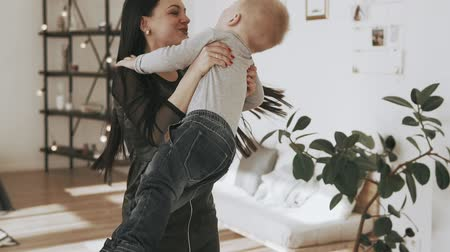 mateřský : Smiling mother and son have fun indoor. Little son in mothers arms at home