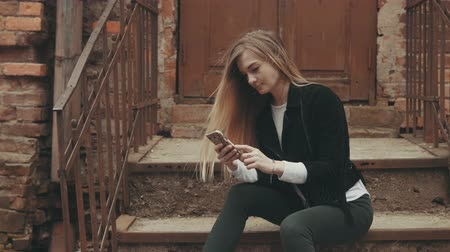 sending : Young woman with smartphone outdoors with copyspace Stock Footage