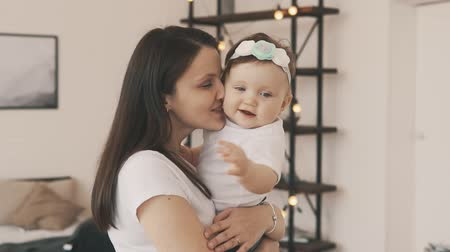 mateřský : Little daughter in mothers arms at home. Smiling mother with baby