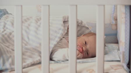 recém nascido : A cute little baby is lying in a bed Stock Footage