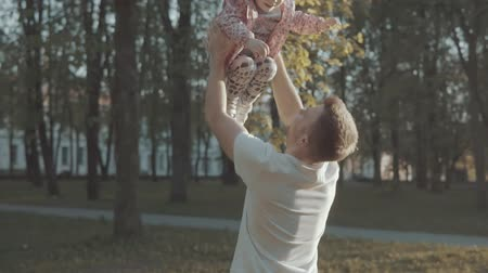 throws : Father throws and catches his daughter in recreation park at sunset Stock Footage