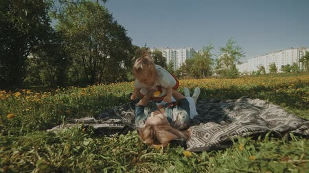 нежный : Mother and daughter lying on lawn. Happiness of motherhood and childhood