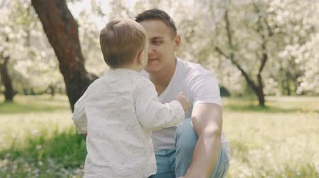 throws : Fatherhood concept. Young father and little son have fun outdoors in slow motion Stock Footage