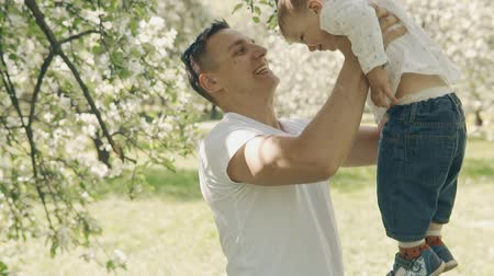 throws : Father raises child in arms and throws up. Young father and son have fun outdoor