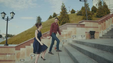 parte : Lovely couple walking upstairs to the right. Smiling boy and girl moving outdoor Stock Footage