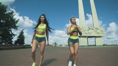 quadriceps : Two Females fitness models doing Lunge workout at city in sunny day