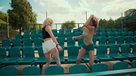 tribune : Two beautiful girls at sunny day have fun and dancing at grandstand in slomo Stock Footage