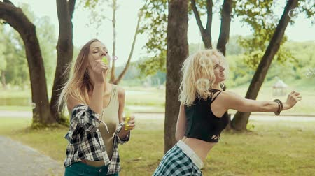 bir genç kadın sadece : Happy hipster girls with sunglasses having fun making bubbles in park Stok Video