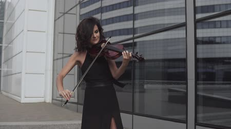 rabeca : Beautiful woman in black dress playing violin near glass building. Art concept Vídeos