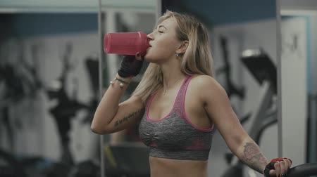 shake hair : Beautiful girl drinking protein in gym. Female drinks water after exercise Stock Footage