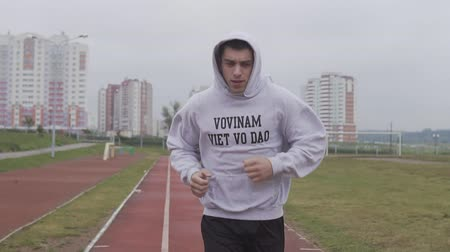 fegyelem : Young man training at stadium in morning. Boxer running in hoodie outdoors