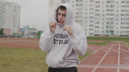 invisible : Young man training in hoodie boxing with invisible opponent at stadium.