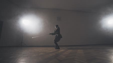 legionary : Medieval warrior training with two-handed sword indoors in slow motion
