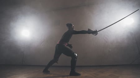 legionary : Medieval warrior training with sword indoors in slow motion