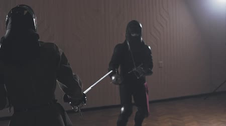 infantry : Medieval warriors are fighting during sword battle indoors in slow motion
