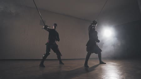 infantry : Medieval warriors training with swords indoors in slow motion