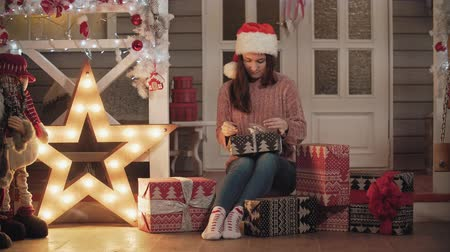 wrapping paper : Attractive girl in santa cap wrapping christmas gifts sitting at house porch Stock Footage