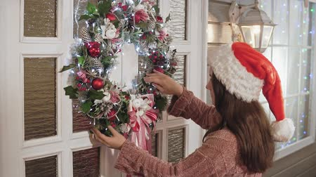 festoon : Attractive female in hat hanging Christmas wreath with balls on door in house