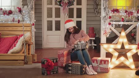 slomo : Girl in santa cap and sweater wrapping christmas gifts sitting at house porch