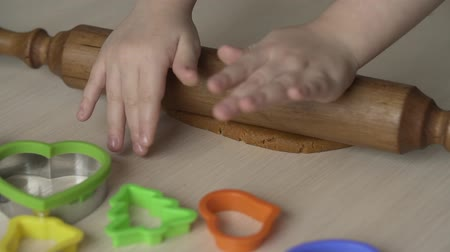 Mother and daughter hands roll dough with rolling pin for christmas cookies