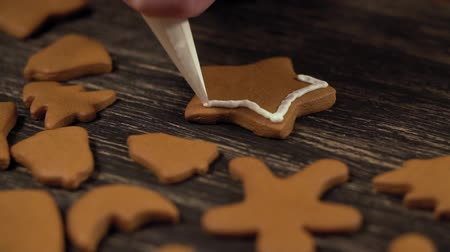 Decoration process of Christmas cookies. Close up garnishing gingerbread star Stock mozgókép