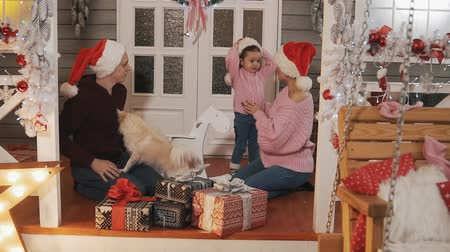 Family pack gifts for Christmas. Family smiling on porch with Christmas decor